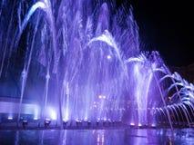 Chorros de agua coloreados en la fuente en la noche con la Luna Llena fotografía de archivo libre de regalías