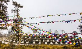 108 chortens. (choertens, stupas) have been erected  at dochula pass at an altitude of more than 3000 m. In the foreground are prayer flags Stock Photos