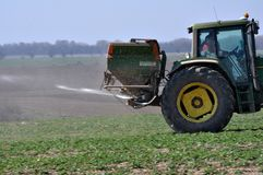 On the field the tractor makes mineral fertilizers. Chortkiv - Ternopil - Ukraine - April 1, 2017. Spring fertilizing fertilizers sowing winter rape in the Stock Photos