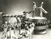 Chorus girls dancing on machine part Stock Photos