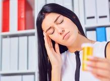 Chory bizneswoman trzyma medyczne pigułki przy miejscem pracy, cierpiący od migreny migreny, czujący bad, bierze medycynę przy zdjęcie stock