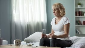 Chory blond damy obsiadanie na łóżku z szkłem woda i pigułki w przodzie, traktowanie obrazy stock