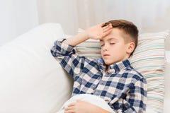 Chory chłopiec lying on the beach w łóżku i cierpienie od migreny zdjęcie royalty free