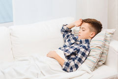 Chory chłopiec lying on the beach w łóżku i cierpienie od migreny fotografia royalty free