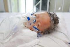 Chory chłopiec stosować wdycha lekarstwo inhalacji maską leczyć Oddechowego Syncytial wirusa RSV na cierpliwym łóżku przy szpital zdjęcia royalty free
