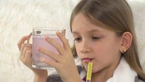 Chory dziecko z pić leki, pigułki, smutna chora dziewczyny twarz z termometrem na kanapie 4K zbiory