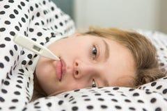 Chory dziewczyny mienia termometr kłaść w łóżku Zdjęcia Stock