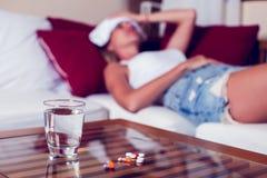 Chory kobiety lying on the beach w łóżku z wysoką gorączką Zimna grypa i migrena obraz royalty free