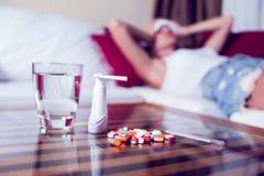 Chory kobiety lying on the beach w łóżku z wysoką gorączką Zimna grypa i migrena obraz stock