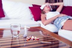 Chory kobiety lying on the beach w łóżku z wysoką gorączką Zimna grypa i migrena obrazy stock