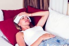 Chory kobiety lying on the beach w łóżku z wysoką gorączką Zimna grypa i migrena fotografia royalty free