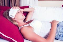 Chory kobiety lying on the beach w łóżku z wysoką gorączką Zimna grypa i migrena fotografia stock