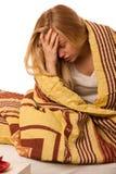 Chory kobiety obsiadanie na bad zawijającym w powszechnej czuciowej bolączce, Zdjęcie Royalty Free