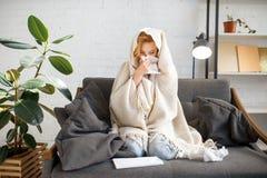 Chory kobiety obsiadanie z chustk? pod koc zdjęcie stock