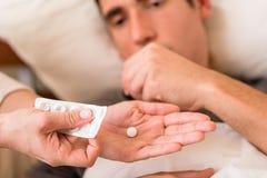 Chory mężczyzna bierze lekarstwo oferował pielęgniarką zdjęcia stock