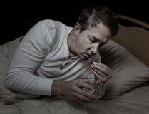 Chory mężczyzna bierze medycynę z wodą Fotografia Royalty Free