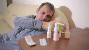 Chory mężczyzna lying on the beach w łóżkowym cierpienie wirusie ma medycyn pastylki pić pigułkę zbiory wideo