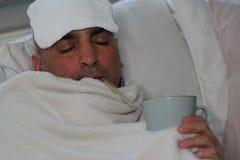 Chory mężczyzna lying on the beach w łóżku pije gorącego napój fotografia stock