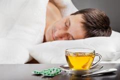 Chory mężczyzna lying on the beach w łóżku z febrą Obraz Stock