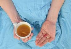 Chory mężczyzna z gorączkową pije filiżanką ciepła herbaty i brać pigułka Grypa sezon Ręki chora mężczyzna mienia pigułka i zdjęcia royalty free