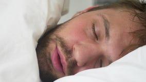 Chory młody człowiek z gorączkowy uśpionym w łóżku, zakrywającym koc zbiory wideo