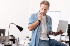 Chory pracownika mienia laptop w lewej ręce Obraz Stock