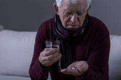Chory starszy mężczyzna bierze medicament Fotografia Royalty Free