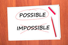 Chose the word POSSIBLE. Crossed out the word IMPOSSIBLE Royalty Free Stock Photos