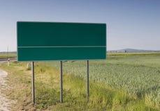 Chose your way billboard in field near road. A blank green road board Stock Photo