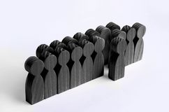 The chosen person among others. A human figure of black color stands out from the crowd. Wooden figures of people. A talented work. Er, a successful choice royalty free stock photos