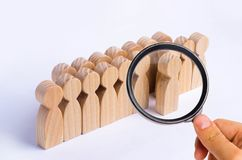 The chosen person among others. A human figure stands out from the crowd. Wooden figures of people. A talented worker, a successful choice. Promotion. Concept stock photography