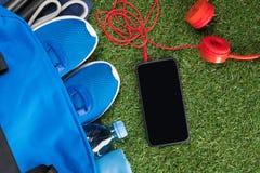 Choses bleues pour des sports et un téléphone avec des écouteurs pour le mensonge s'exerçant sur une herbe verte Photos stock