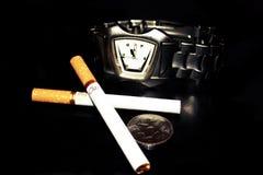 Choses de cigarette, de montre-bracelet et d'une pièce de monnaie que j'ai besoin pendant une bonne vie Images stock