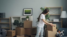 Choses de transport de fille et de type dans des boîtes pendant la relocalisation en nouvel appartement banque de vidéos