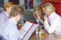 Chosing from a menu. A group of four people choosing dishes from the menu in a restaurant royalty free stock photo