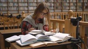 Chosing um livro na biblioteca vídeos de arquivo