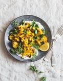 Chou-fleur rôti de safran des indes avec le habillage grec de yaourt Nourriture saine délicieuse sur un fond gris photographie stock