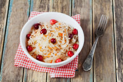 Choucroute ou chou aigre avec des canneberges dans une cuvette blanche sur la table en bois rustique images libres de droits