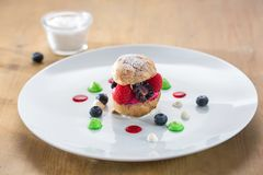 Choux bun with fruits in a white plate royalty free stock photos