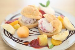Choux cream ice cream with fruits. On a plate stock images