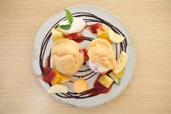 Choux cream ice cream with fruits. On a plate royalty free stock photo