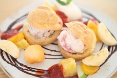 Choux cream ice cream with fruits. On a plate stock image