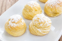 Choux cream with icing topping on white plate. Stock Image