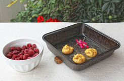 Choux a la creme 7. Homemade choux raw pastry ball placed on metal baking tray and bowl of fresh raspberries Royalty Free Stock Images