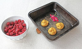 Choux a la creme 6. Homemade choux raw pastry ball placed on metal  baking tray and bowl of fresh raspberries Royalty Free Stock Image