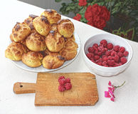 Choux a la creme 12. Homemade unfilled choux pastry ball and bowl of fresh raspberries Stock Images