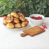 Choux a la creme. Homemade unfilled choux pastry ball and bowl of fresh raspberries Royalty Free Stock Photography