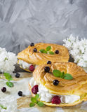 Choux pastry with cream, raspberry, black currant and mint. On the wooden table and parchment with lilac flowers Royalty Free Stock Images