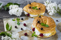 Choux pastry with cream, raspberry, black currant and mint. On the wooden table and parchment with lilac flowers Royalty Free Stock Photography