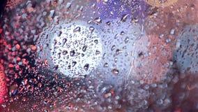 Chova as gotas em uma janela de carro, sinais blured no fundo video estoque